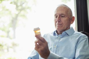 Man looking at a prescription pill bottle