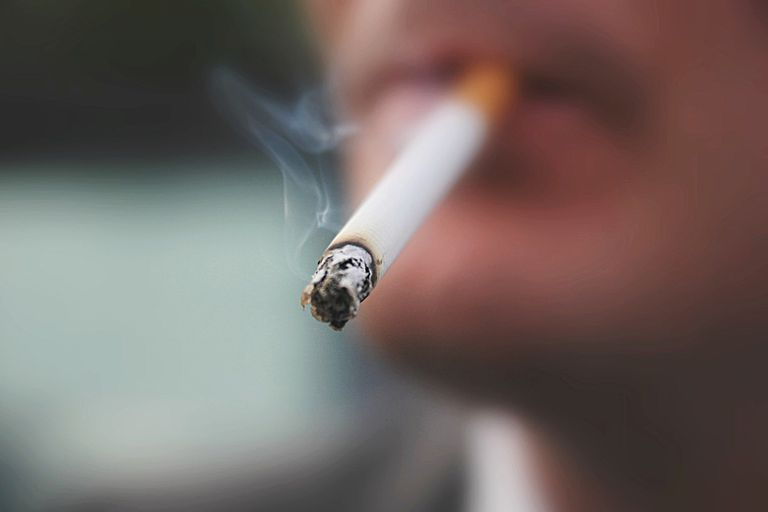close up of man smoking a cigarette