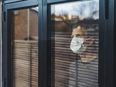 man face mask behind window closed door