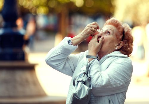 Older age woman putting drops in her eye