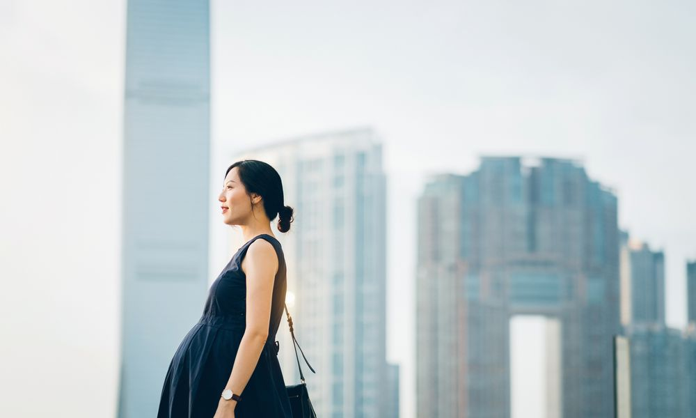 Beautiful pregnant Asian woman standing against modern cityscape enjoying view