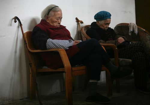 Photo of two senior women napping in chairs