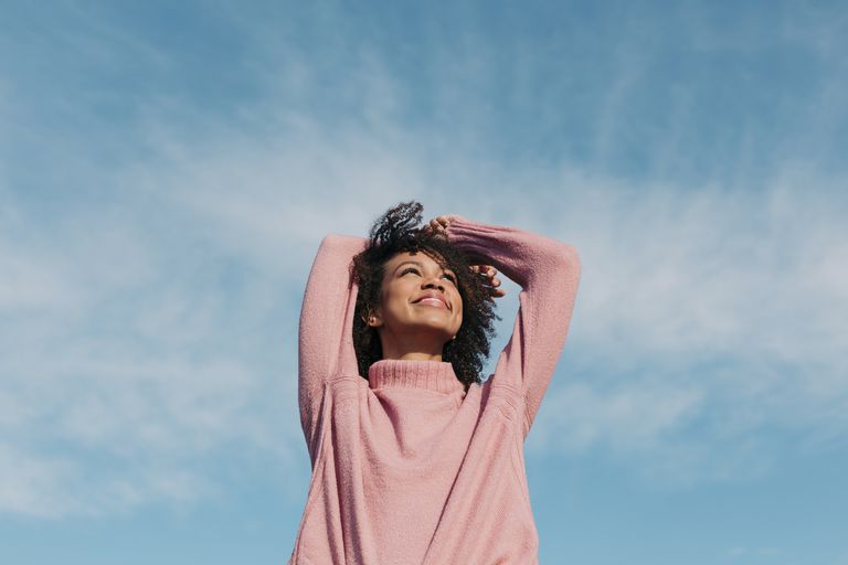 woman in pink sweater smiling under a blue sky