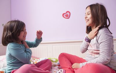 Girls playing on a bed.