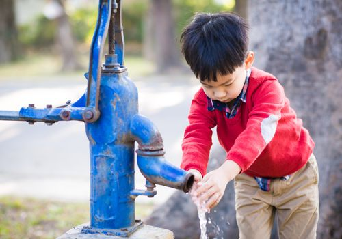Young boy washing his hands at an outdoor spigot