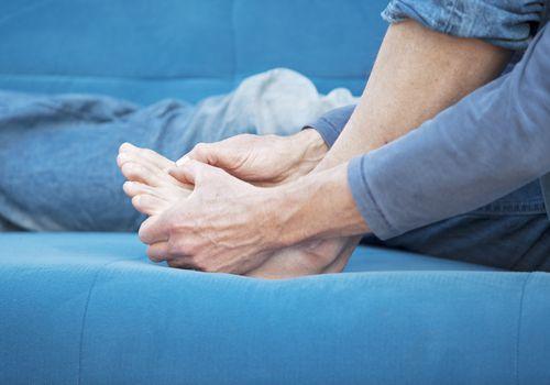 A man massaging his toe cramps