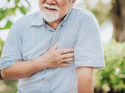 Senior man holding his chest and feeling pain