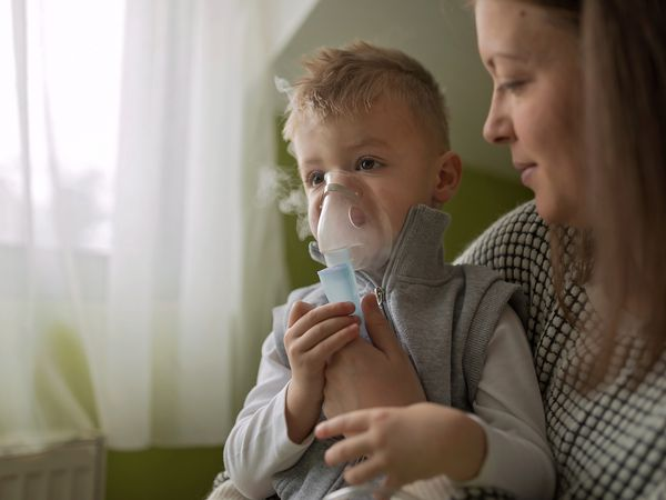 Woman helping child using nebulizer mask