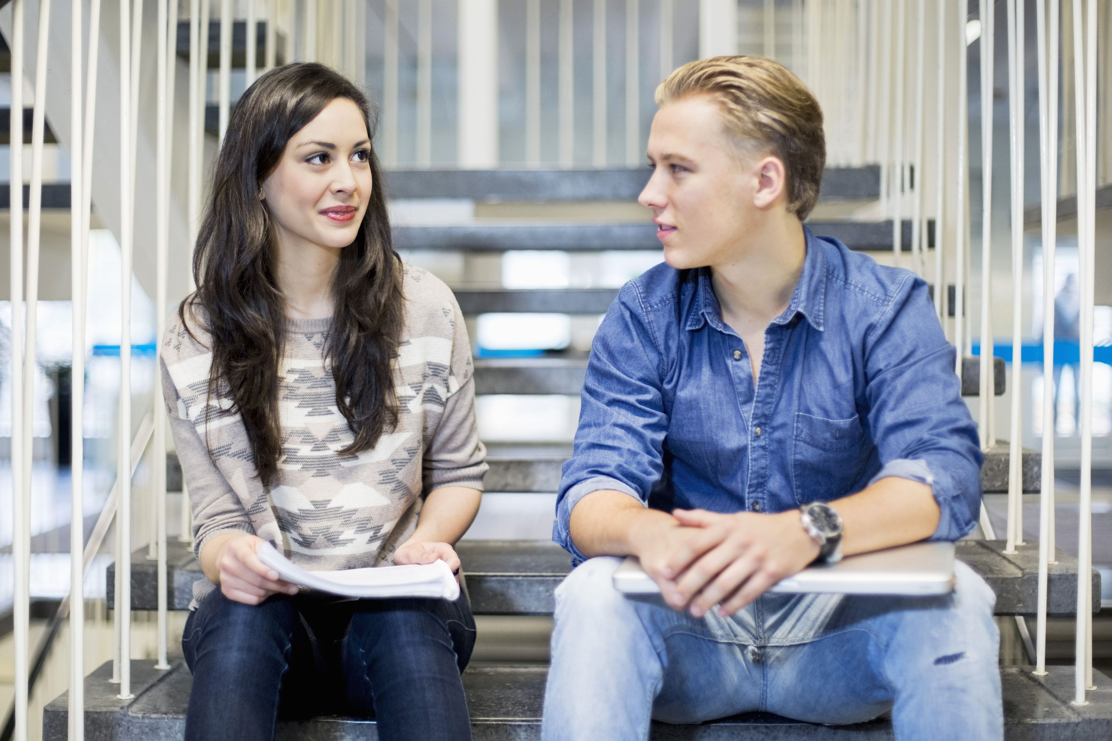 College aged man and woman sitting on school steps talking