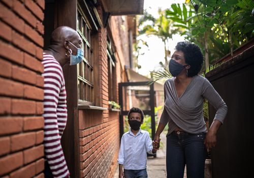 Two neighbors meeting up to talk with masks on.