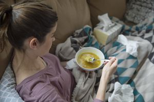 Sick woman eating soup on the couch
