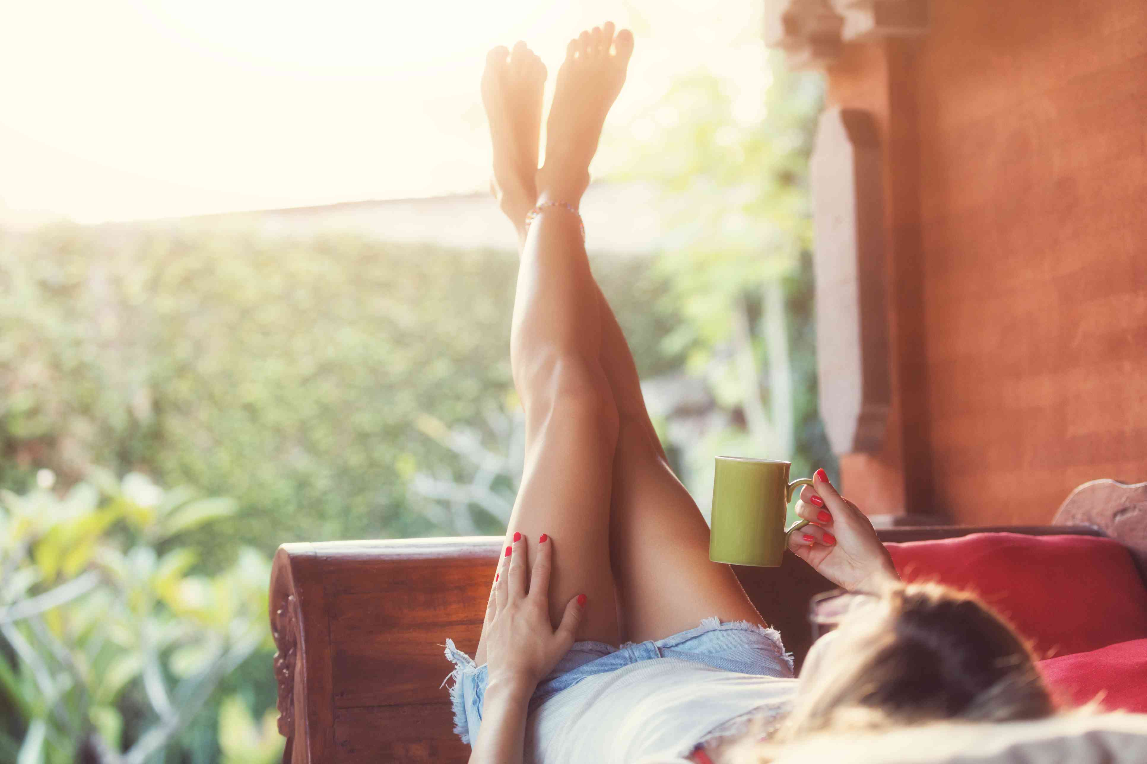 Woman drinking coffee and enjoying the morning sunlight in garden