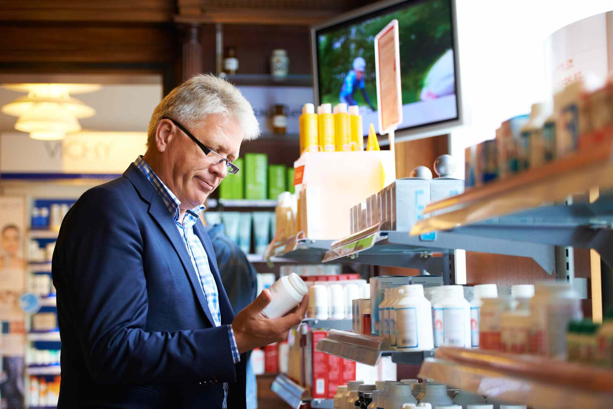 Man reading label on medicine in store
