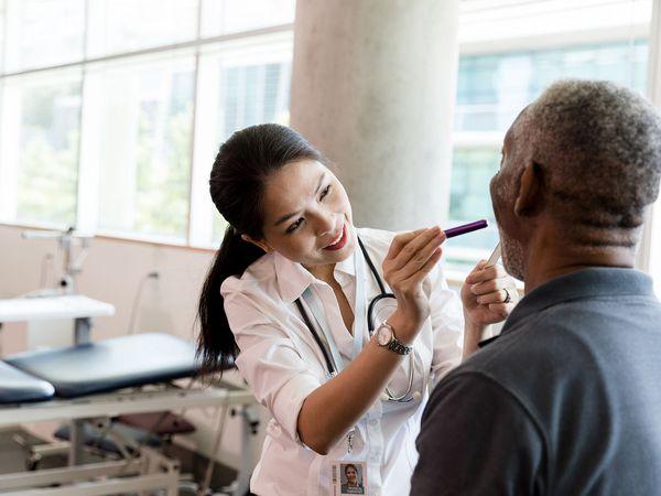 Female doctor examines a senior man's throat