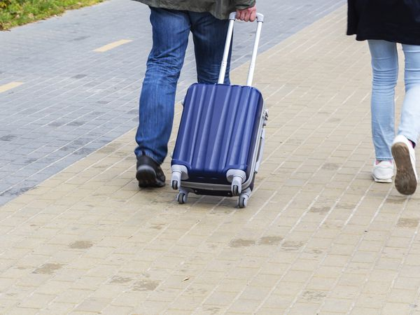 A person with a rolling bag walking next to a companion.