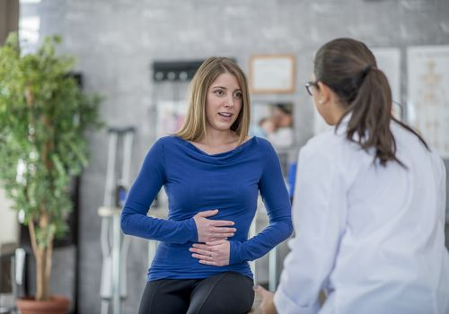 Woman complaining of A Stomachache to her doctor