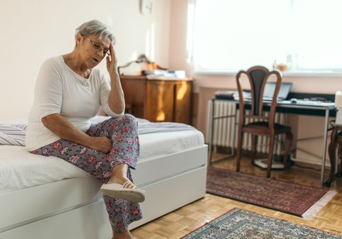 A senior woman experiencing dizziness, sitting on the edge of her bed