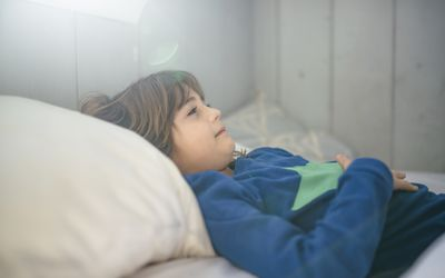 Kid in pajamas lays in bed feeling sick, stomachs