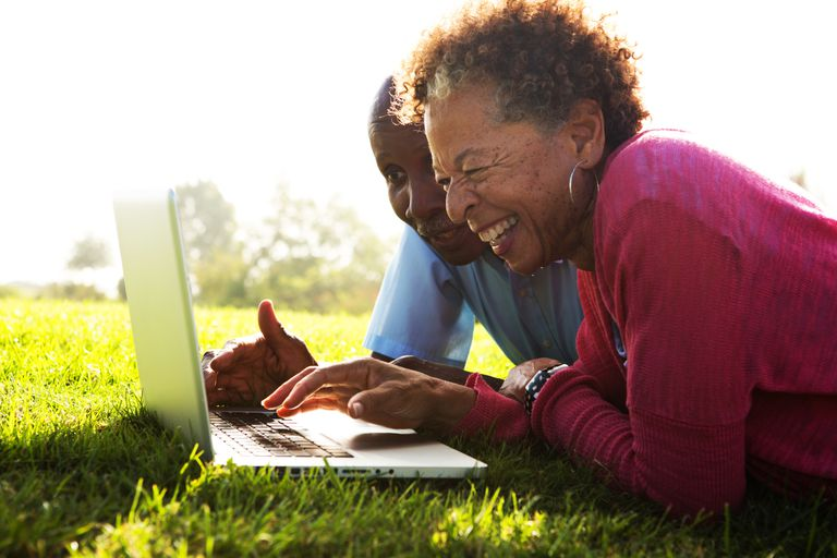 Older couple using laptop computer outside