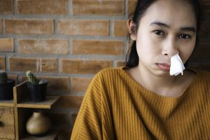 Portrait Of Ill Young Woman With Tissue In Nose Against Brick Wall