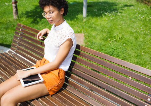 Woman sitting on park bench outside