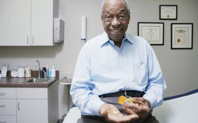 man at doctor's office holding pills and prescription bottle