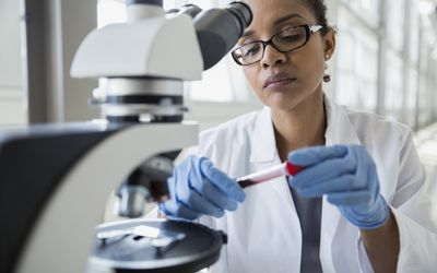 Scientist at microscope examining blood sample test tube