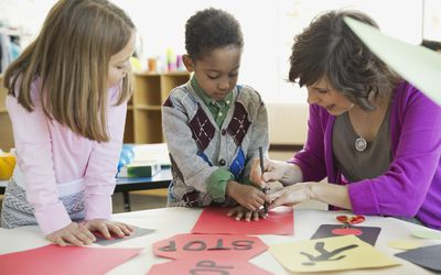 Teacher helping students make art