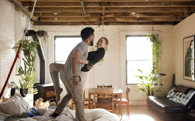 Cheerful multi-ethnic couple dancing on bed at home