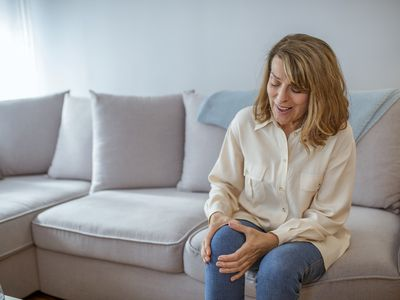 Mature woman in pain, holding knee