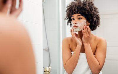 Teenage Girl Applying Facial Mask While Looking In Mirror At Bathroom - stock photo