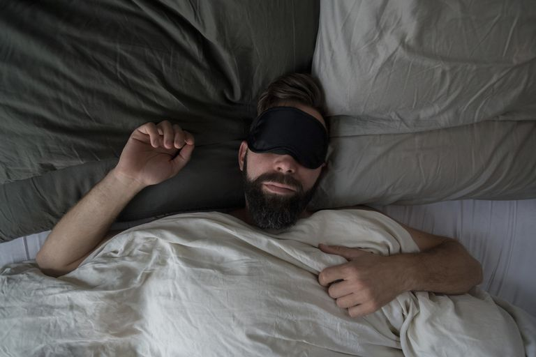 A man sleeping in his bed at home