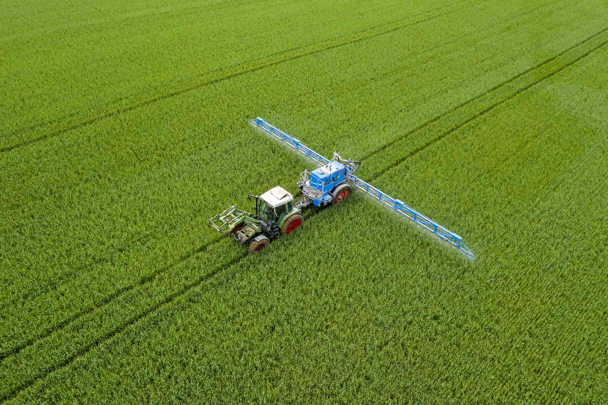 Aerial view of rtactor spraying wheat field