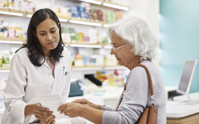 Customer showing prescription to female doctor