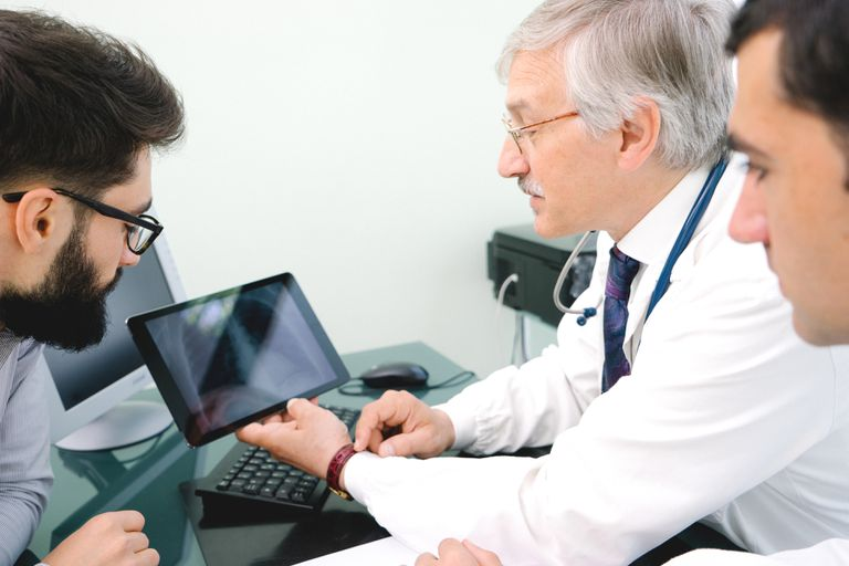 Mature Male Doctor Using A Digital Tablet For His Diagnosis.