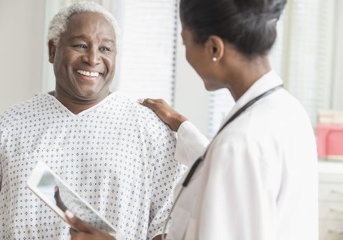 A Black doctor putting her arm on a Black male patient