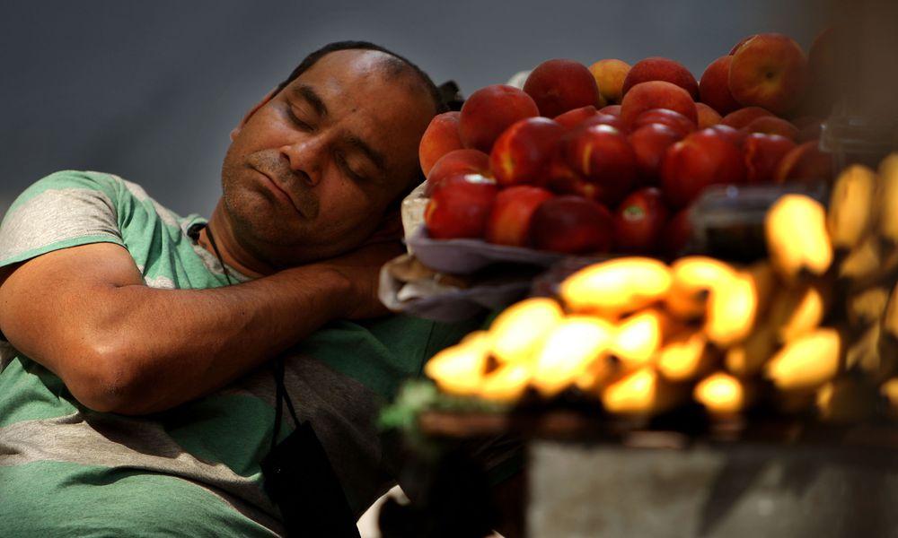 A man sleeps next to fruits