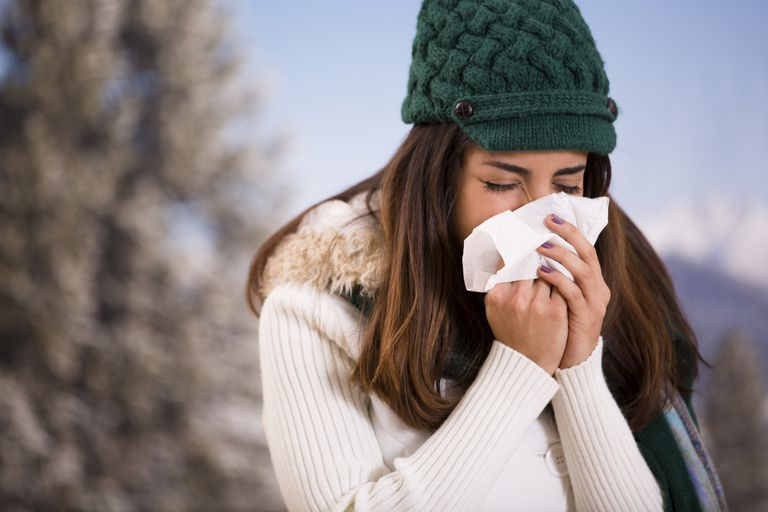 Latin woman with flu or allergies sneezes while outside. Winter.