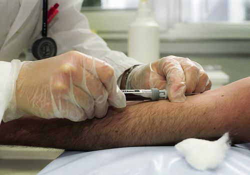 A male nurse draw a sample of blood from a patient's arm