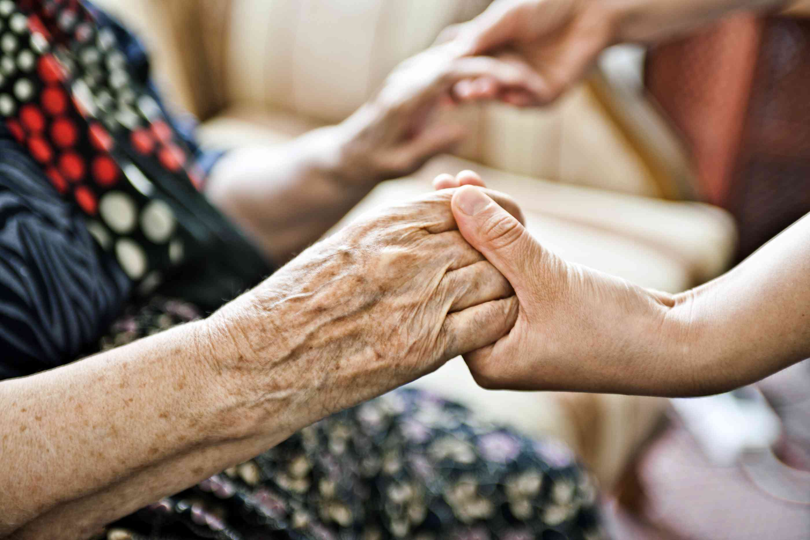 Older adult holding hands with another person
