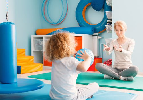Occupational therapist playing catch with young child