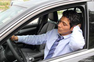 man falling asleep behind the wheel of a car