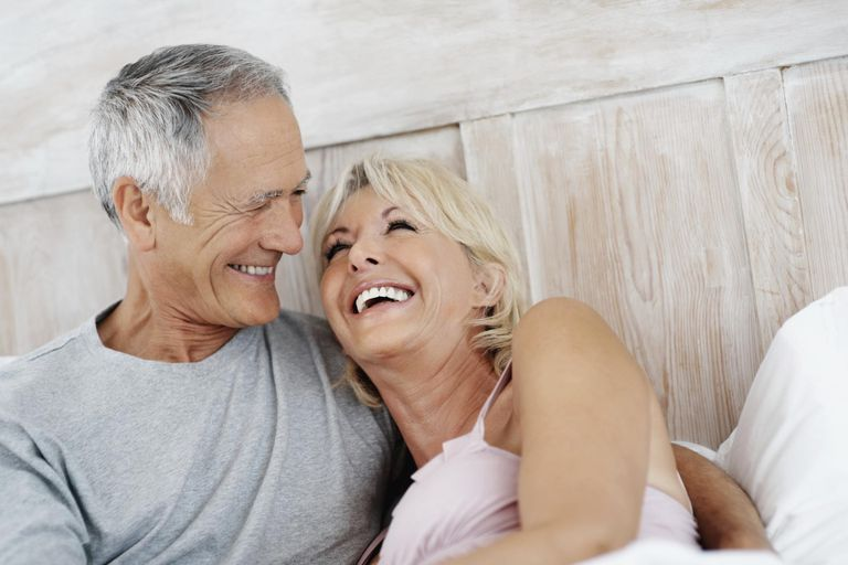 Joyful mature female resting on senior man's shoulder