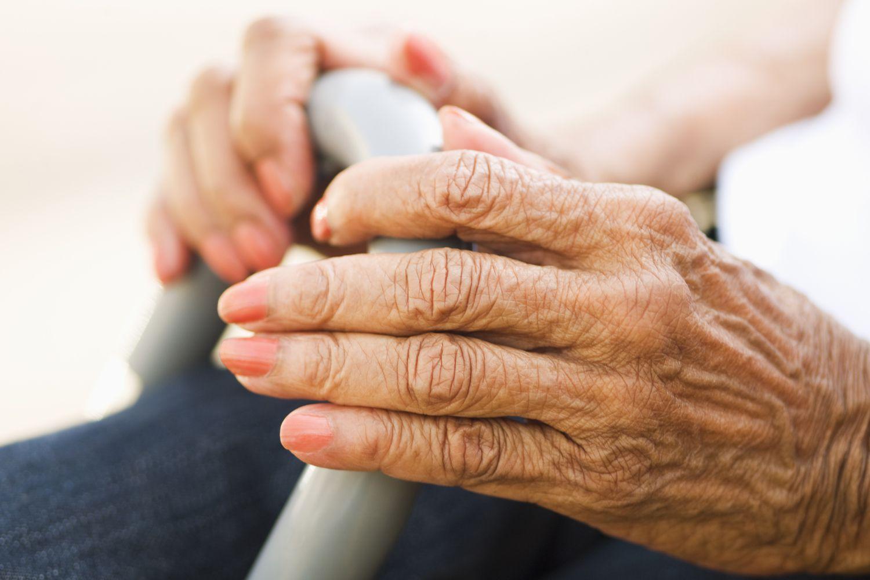 An elderly woman with arthritic hands.