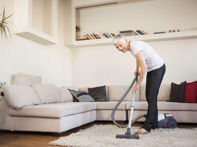 Senior woman vacuums