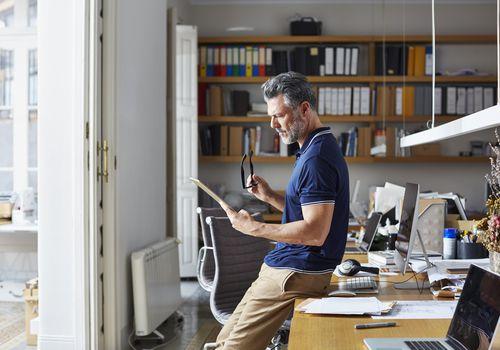Businessman using digital tablet leaning on desk