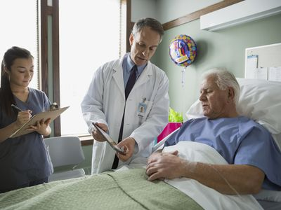 Doctor speaking with elderly man in hospital bed