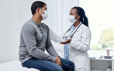 Doctor consulting a patient, both wearing face masks.