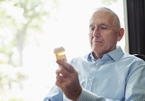 Man looking at a prescription pill bottle
