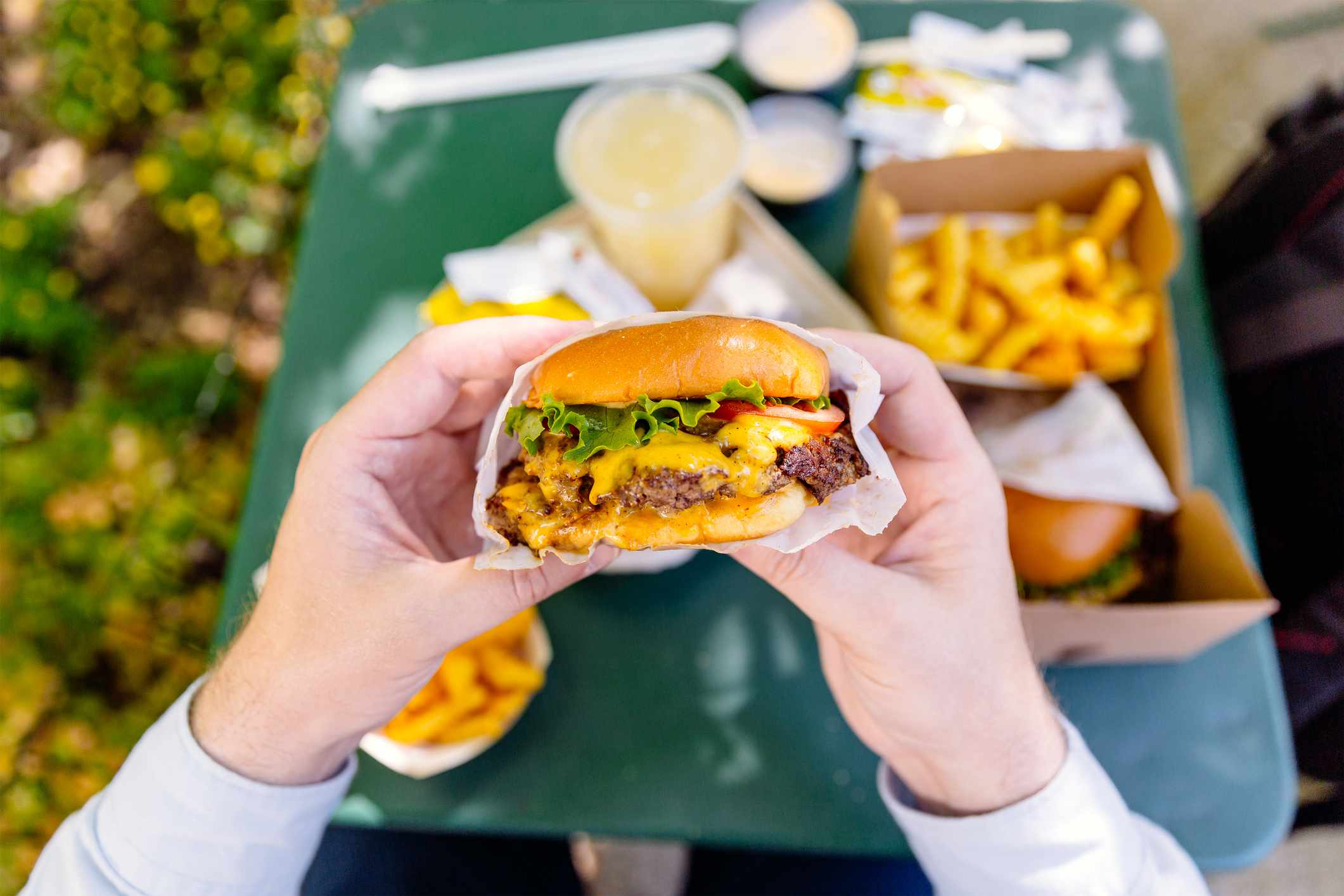 Man eating cheeseburger, personal perspective view with other fast food on the table